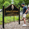 Joshua Rodriquez's son, Enrique Rodriquez, smiles at his father's portrait on the sign in front of the garden named in his honor. Staff Photo By Josh Hicks