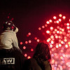 A boy sits atop his father's shoulders for a better view of the Thunder fireworks on Saturday. Staff Photo By Josh Hicks