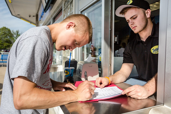 Chad Sogge, 17, left, signs a petition that was started by Harry Knable, right, to name Silver Street Park's soccer field after Jacob Trulock in his honor. Staff Photo By Josh Hicks