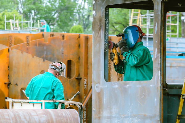 A Jeffboat employee grinds steel around a barge window on Thursday. Staff Photo By Josh Hicks