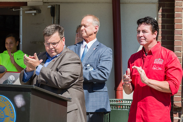 From left, Bill Burns, president of the parks authority, Jeffersonville Mayor Mike Moore, and Papa John's Pizza founder and CEO John Schnatter clap during the dediction ceremony at the newly named John H. Schnatter Nachand Fieldhouse on Wednesday.