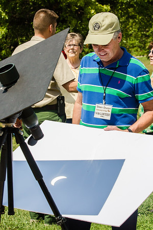 Falls of the Ohio volunteer Stan Dunn uses a telescope to project the image of the eclipse onto a poster board.