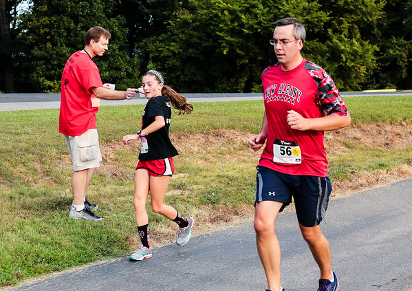 The fastest future alumn from the graduating class of 2023, 7th grader Lila Endres, grabs a cup of water from Jason Harvey as she runs with her father Justin Endres, far right, during the New Albany Alumni walk/run at Sam Peden Community Park.