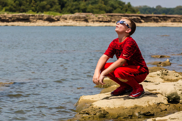Tyler Reynolds squats on the edge of the Falls of the Ohio took look up at the solar eclipse on Monday. Staff Photos by Josh Hicks