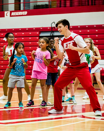 Logan Houchin leads some young cheerleaders in a dance to warm them up before they learn cheers at Jeffersonville High School.