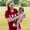 Amanda McLaughlin says she decided to ditch her stroller on the last leg of the New Albany Alumni walk/run and carry her daughter Emme through the finish line.