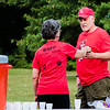 Diane Ried hands a cup of water to Chris Rasmussen during the New Albany Alumni walk/run at Sam Peden Community Park.