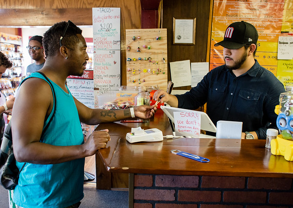 Fred English exchanges two tickets with the owner of La Tiendita On Market Daniel Martinez for two tacos during the Taco Walk in New Albany on Saturday. Staff Photos By Josh Hicks