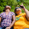 Breanna Hall, left, sits with her mother Devon Hall as they fix their shielded eyes on the solar eclipse at the Falls of the Ohio on Monday.