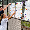 "Jacob Fico, left, and his sister Olivia Fico, of Kentucky, hang up ""Welcome Home"" signs for all of the Floyds Knobs Little League Softball team members. The Fico's sister played travel softball with a lot of the girls on the Floyds Knobs team and went with them on the 10 day trip."
