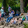 Groups of people sit on the rock beds at the Falls of the Ohio for a unique eclipse viewing place.