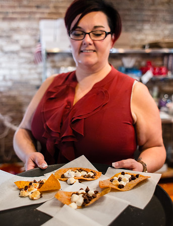 Adrienne & Co. bakery front of house manager Paula Atkins serves up a tray of chocolate and marshmallow tortilla treats during the Taco Walk in New Albany on Saturday.