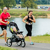 Ben Plume and Jennifer Whittier run with their son Oliver Plume in the first-ever New Albany High School alumni walk/run at Sam Peden Community Park on Saturday.