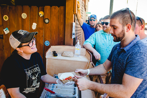 Floyd County Brewing Company owner Julie Hampton serves a taco to Matt Wilson during the Taco Walk in New Albany on Saturday.