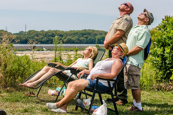 Falls of the Ohio staff members Dani Cummins, Candace Hilderbrand and Kenny Karem and volunteer Lucas Green look up fifteen minutes after the eclipse began.