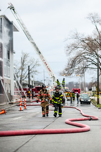Firefighters walk along a hose during the Breakwater Apartment fire on Saturday. Staff Photo By Josh Hicks