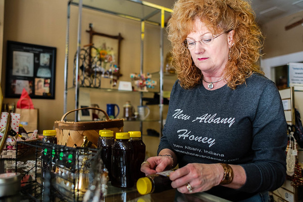 Terri Lynch applies labels to bottles of New Albany Honey at her store Pearls on Pearl in New Albany. Staff Photo By Josh Hicks