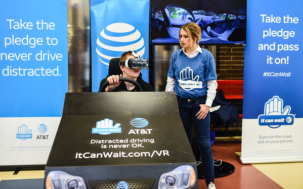 Freshman Andrew Smith tests out the AT&T virtual reality distracted driving simulation with Roseileen Fitts at Jeffersonville High School on Monday morning. Staff photo by Tyler Stewart