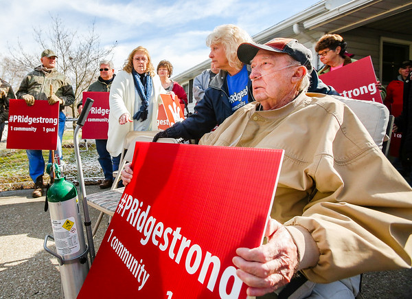 William King, far right, who has lived in Pleasent Ridge since 1976, holds a sign during the press announcement of a major development in the residents' lawsuit against the city of Charlestown in a neighborhood driveway on Friday. Staff Photo By Josh Hicks