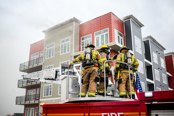 Georgetown firefighters gear up before running the ladder up to the northeast corner of the Breakwater Apartments. Staff Photo By Josh Hicks