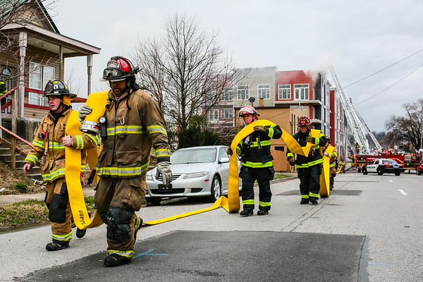 New Albany and Georgetown firefighters run a supply hose to a hydrant east of the Breakwater Apartments on Saturday. Staff Photo By Josh Hicks