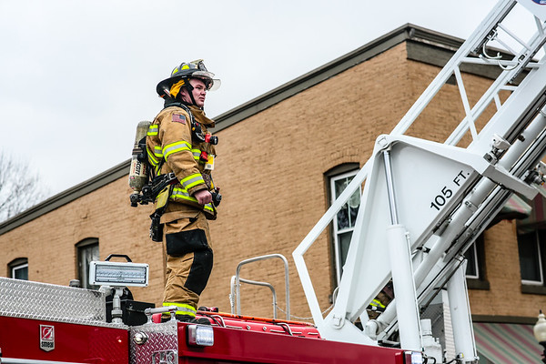 A Georgetown firefighter stands on top of a fire engine, gazing at the billowing Breakwater Apartments. Staff Photo By Josh Hicks