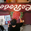 "Annie Wilkinson paints in flower details on the ""Le Rose"" theater sign for the Clark County Museum on Wednesday. The theater is to feature historical films. Staff Photo By Josh Hicks"