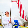 "Adam Sandifer hoists the American Flag as ""The Star Spangled Banner"" plays before the Special Olympic Polar Plunge at Deam Lake in Borden on Saturday. Staff Photo By Josh Hicks"