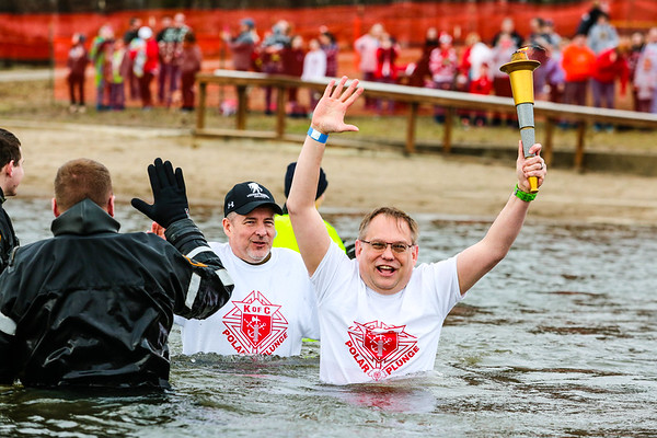 Torch Bearer for the the Special Olympic Polar Plunge Patrick Murta keeps the flame alive as he wades through Deam Lake in Borden on Saturday. Staff Photo By Josh Hicks