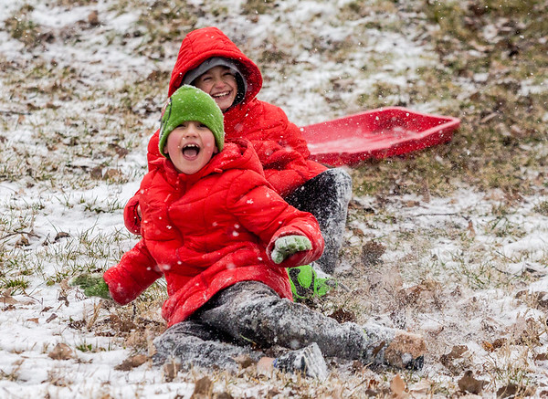 Joshua, 8, in the green hat, and his brother Mason, 10, fly out of their sled at Ashland Park in Jeffersonville on Thursday. Staff Photo By Josh Hicks