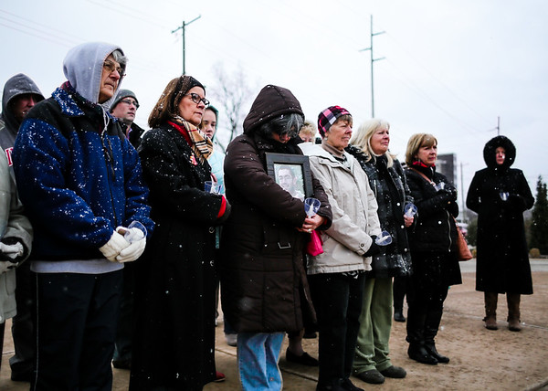 A group of people gather at the base of the Big Four Bridge on Sunday for a Clark County Cares candlelight vigil honoring those who lost their lives to drug addiction. Staff Photo By Josh Hicks