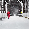 Jerrie Barber, 71, treks across the Big Four bridge through Thursday morning's snow shower, leaving behind a fifth string of shoeprints over the Ohio River. Barber, Minister of the Northside Church of Christ in Jeffersonville, says he usually doesn't wear shoes and has ran over 4,000 miles barefoot. Staff Photo By Josh Hicks