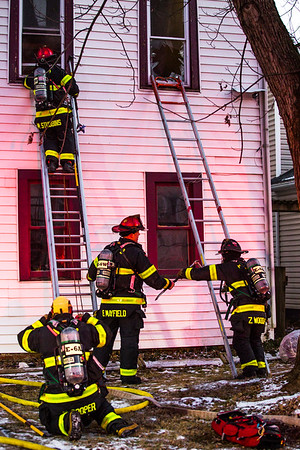 Firefighters grab tools and hoses as they climb up to the second story of the house that caught fire on the 1700 Block of East Elm Street on Saturday. Staff Photo By Josh hicks