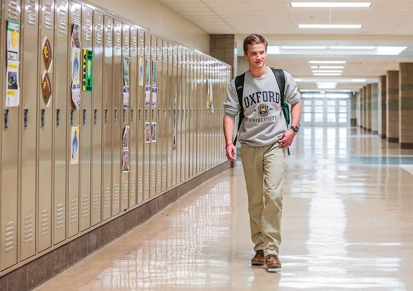 Carson Conley walks down a row of lockers at Floyd Central High School. Staff Photo By Josh Hicks