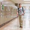 Carson Conley walks down a row of lockers at Floyd Central High School. Staff Photo By Josh Hicks