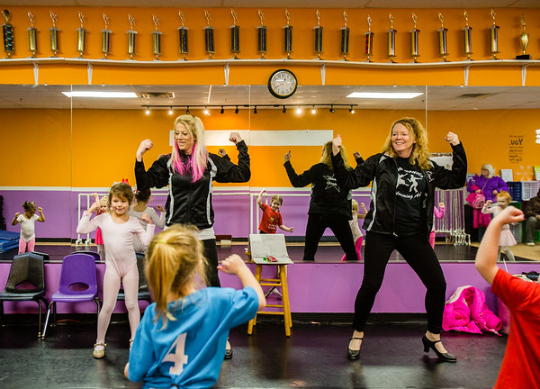 (from left) Serena Scott, 6, helps her mother Alicia Corcoran and grandmother Patty Simmonds' teach preschoolers how to dance at the Simmonds Dance Studio in Jeffersonville on Saturday. Staff Photo By Josh Hicks