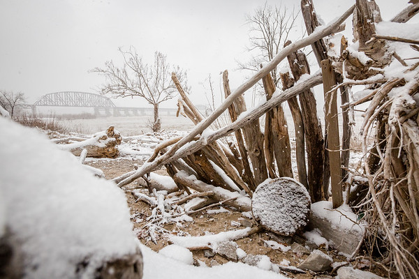 A tiny shelter on the bank of the Falls of the Ohio collects snow as the tide rages in the background. Staff Photo By Josh Hicks