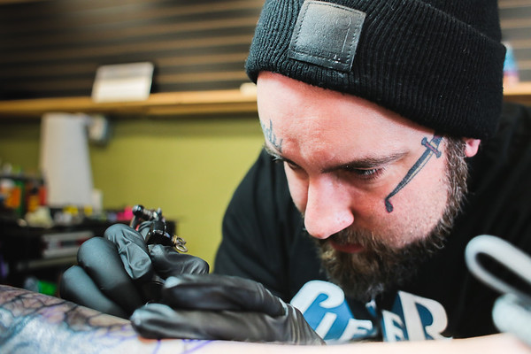 Greg Mosier, a tattoo artist at Tattoo Machine Gun, has had his hands on ink for 14 years. Pictured, Mosier focuses on a calf tattoo inspired by the movie Alien at Tattoo Machine Gun in Jeffersonville on Friday. Staff Photo By Josh Hicks