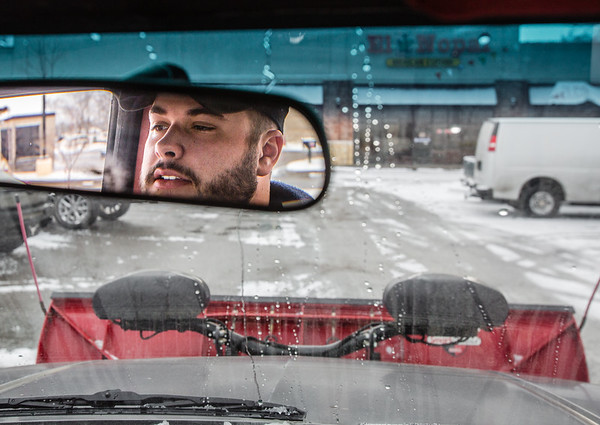Jake Harbin keeps an eye out for pedestrians and fellow motorists as he plows off the last bit of snow and ice in a Jeffersonville Parking lot on Thursday. Staff Photo By Josh Hicks
