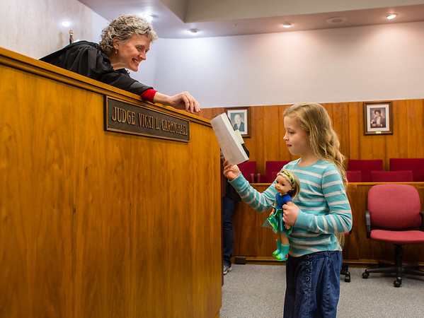 Sophia Reed, 9, receives an adoption certificate from Judge Vicki Carmichael for her doll after promising to take care of her at the Clark County Government Building on Saturday. Kids were invited to Circuit Court 4 to adopt dolls, action figures or pets. Staff Photo By Josh Hicks
