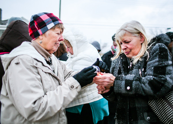 Pam Weber, left, lights her candle from Terri Poff's flame during the Clark County Cares candlelight vigil honoring those who lost their lives to drug addiction at the base of the Big Four Bridge on Sunday. Staff Photo By Josh Hicks