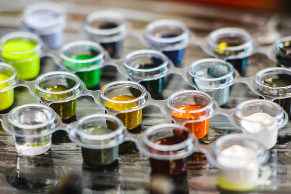 A row of ink cups hold vibrant colors at Tattoo Machine Gun in Jeffersonville on Friday. Staff Photo By Josh Hicks