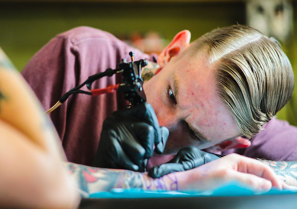 Joshua Morgan needles in a decorative wrist piece onto Austin Lincks at Tattoo Machine Gun in Jeffersonville on Friday. Staff Photo By Josh Hicks