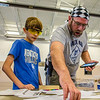 Julian Caffey, 12, and his father, David Caffey work on finding a design for Julian's Pinewood Derby race car at the Clarksville Fire Department on Saturday. Staff Photo By Josh Hicks