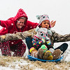 Cheyenne, 13, and her little sister Aspen, 3, get a push down the hill from their mother behind a flood wall in Jeffersonville on Thursday. Staff Photo By Josh Hicks