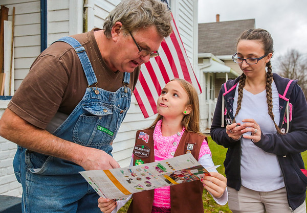 As soon as she got off the bus after school on Wednesday, Jade, 9, took to the sidewalks, knocking on doors to sell Girl Scout Cookies for her Kentuckiana Troop #1647. Kevin Milburn, left, eagerly points out the types of cookies he would like to purchase from her, while Jade's mother, Casey Lemarr, right, shows her support. This year marks Jade's first go at selling cookies, and she has already sold over 100 boxes. Staff Photo By Josh Hicks