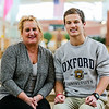 DeAnn Conley-Trasher, left, and her son Carson Conley sit on a bench at Floyd Central High School. Carson has received a perfect score on the ACT—twice—followed by acceptance letters from Oxford and Princeton. His mother teaches Special Education at Floyd Central. Staff Photo By Josh Hicks