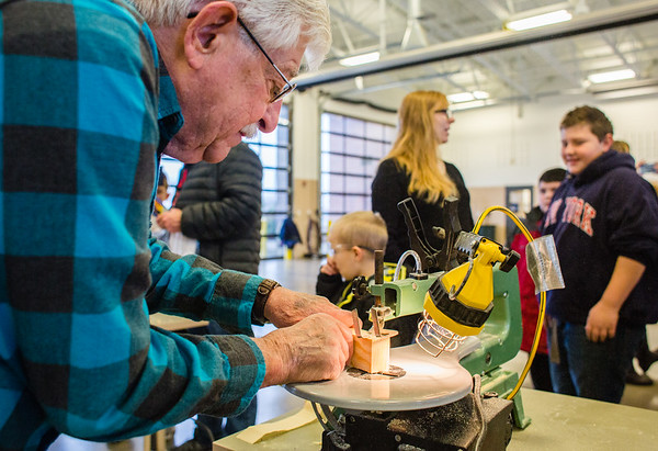 Jack Notes focuses a skill saw through a section of an undeveloped Pinewood Derby race car on Saturday. Staff Photo By Josh Hicks