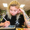 Tattoo artist Kayla Byron sketches on a tablet at Tattoo Machine Gun in Jeffersonville on Friday. Staff Photo By Josh Hicks