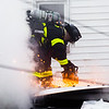 A New Albany firefighter saws into the roof of a burning house on the 1700 Block of East Elm Street on Saturday. Staff Photo By Josh Hicks